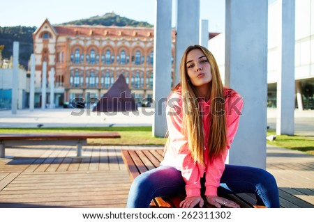 Portrait of attractive school girl posing for camera while giving a kiss, charming caucasian student sitting on the wooden campus bench against university building, cheerful teenager