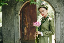 Portrait of attractive serious young woman in traditional Vietnamese dress and headwear holding lotus flowers and looking at camera