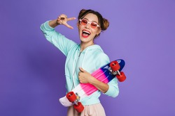 Portrait of attractive skater girl with two buns in sunglasses holding skateboard and showing peace sign isolated over violet background in studio