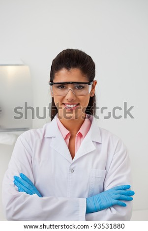 Portrait of attractive smiling female dentist with hands folded