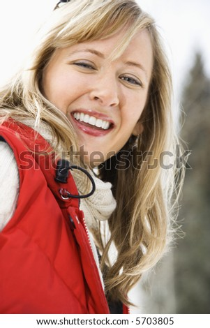 Portrait of attractive smiling mid adult Caucasian blond woman wearing red ski vest looking at viewer.