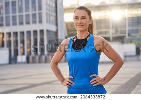 Portrait of attractive sportive middle aged woman in sportswear looking away, standing outdoors ready for running in the city