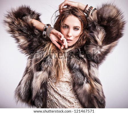 Portrait of attractive stylish woman in fur against grey background.