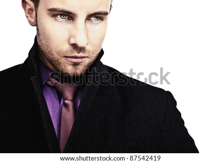 Portrait of attractive & successful young business man in black coat.