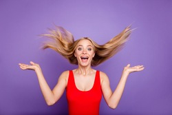 Portrait of attractive surprised blonde gorgeous girl wearing red swim suit with opened mouth, wind blows hair. Isolated over violet pastel background