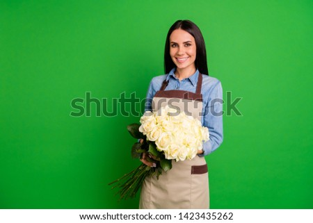 Portrait of attractive sweet lovely lady assistant salesperson hold hand rosebud wear trendy stylish blue shirt denim jeans feel positive cheerful successful isolated green background #1423435262