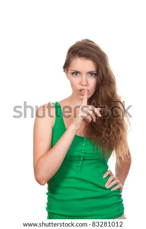 portrait of attractive teenage girl with finger on lips, brown long hair, isolated over white background concept of student show quiet, silence, secret gesture, young pretty woman