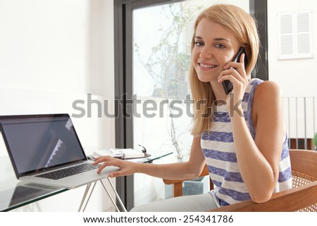 Portrait of attractive teenager girl student at her work desk at home, using smartphone technology in conversation, and a laptop computer to work. Professional woman with mobile phone indoors.