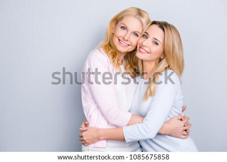 Portrait of attractive trendy stylish cute cheerful similar mother and daughter in casual outfit hugging isolated over grey background beaming smiles
