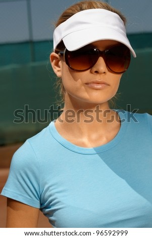 Portrait of attractive woman at summer in tennis outfit and sunglasses.?