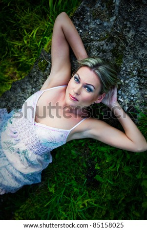 Portrait of attractive woman in blue sundress lying on stones at summer morning