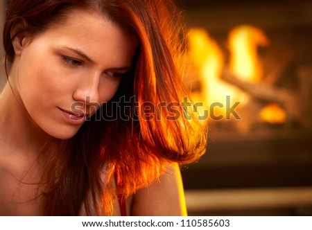 Portrait of attractive woman looking down, daydreaming in front of fireplace.