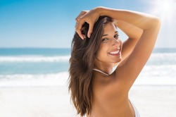 Portrait of attractive woman standing at beach and looking at camera. Happy smiling girl relaxing at seaside during summer vacation. Closeup of beautiful young latin woman with copy space.