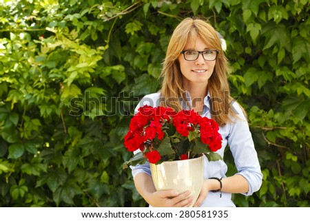 Portrait of attractive woman standing at garden at home while looking at camera and holding potted flower in her hands.
