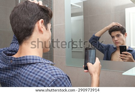 Portrait of attractive young adolescent teenager man using a smartphone device to take selfies pictures of himself in a home bathroom mirror, networking in social media. Technology lifestyle at home.