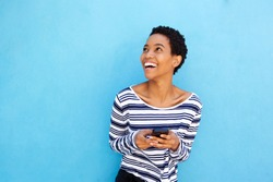 Portrait of attractive young african american woman holding cellphone by blue wall
