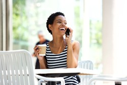 Portrait of attractive young african woman drinking coffee and talking on mobile phone at outdoor cafe