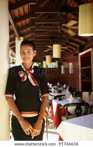 Portrait of attractive young asian woman working as waitress in exclusive restaurant. Waist up, front view