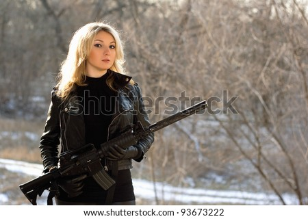 Portrait of attractive young blonde with a gun