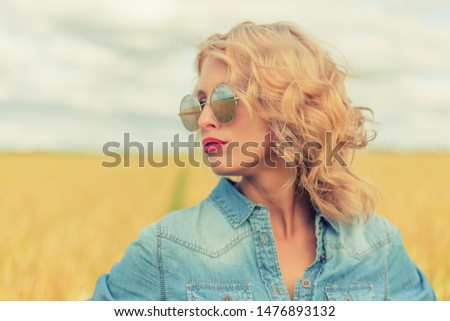 Portrait of attractive young blonde woman in summer day