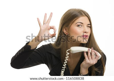 Portrait of attractive young business woman gesturing okay sign after successful deal on phone over white background.