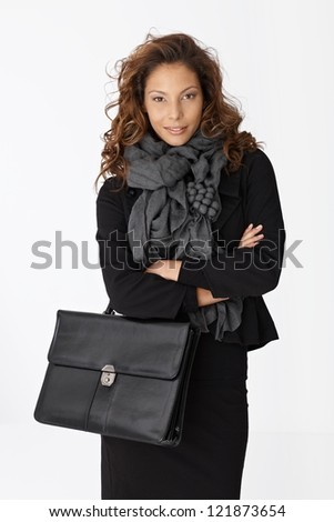 Portrait of attractive young businesswoman holding briefcase, smiling.