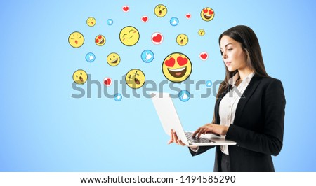 Portrait of attractive young businesswoman using laptop with emotive on subtle blue background. Communication and emotion concept