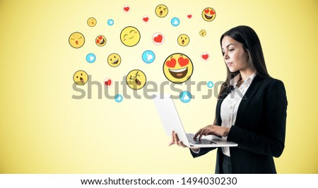 Portrait of attractive young businesswoman using laptop with emotive smileys on yellow blue background. Communication and emotion concept