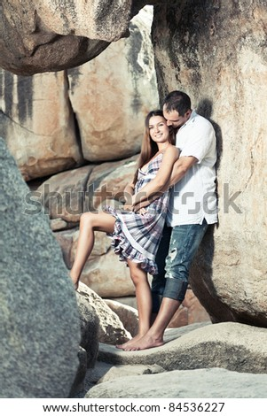 portrait of attractive young couple on the cliff. - stock photo