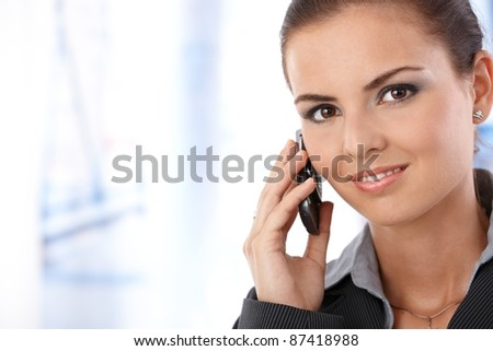 Portrait of attractive young female on phone call, smiling, looking at camera.?