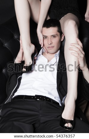 Portrait of attractive young man embracing woman's perfect legs