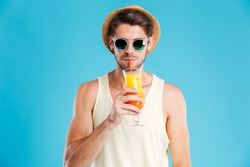 Portrait of attractive young man in hat and sunglasses standing and drinking orange juice over blue background