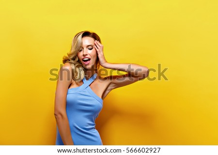 Portrait of attractive young model with blonde hair wearing blue dress against of yellow background.Isolated - Shutterstock ID 566602927