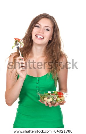 Portrait of attractive young smile woman eating vegetable salad, holding bowl and fork in hand, isolated over white background