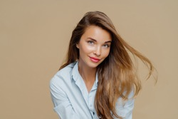 Portrait of attractive young woman has fair hair floating in wind, natural beauty, wears makeup, dressed in stylish shirt, isolated over brown background, has healthy skin. People, style, feminity