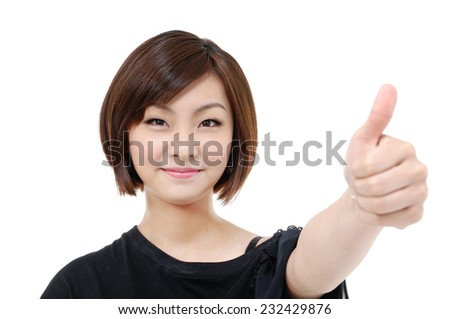Portrait of attractive young woman laughing at camera with thumbs up.
