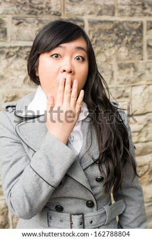 Portrait of attractive young woman looking surprised and trying to cover mouth