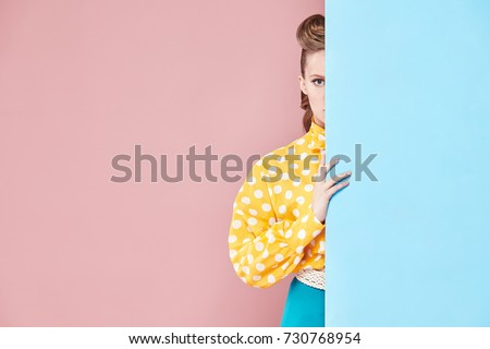Portrait of attractive young woman model wearing yellow blouse with white polka-dot, blue skirt in pin-up style, hiding behind light blue wall in studio with blue and pink background