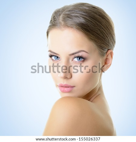 Portrait of attractive young woman over blue background