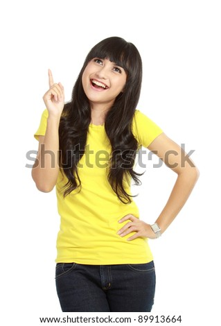 Portrait of attractive young woman pointing up over white background - stock photo