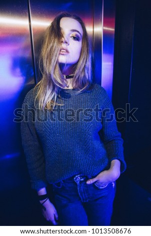 Stock Photo Portrait of attractive young woman posing in the photoshoot. Club with neon lights