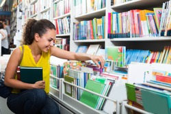 portrait of attractive young woman selecting textbooks for school in book shop