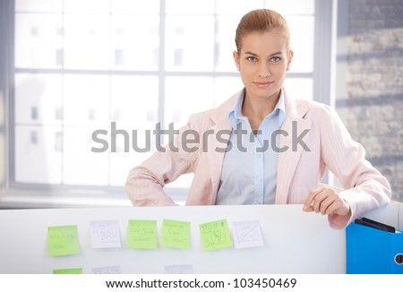 Portrait of attractive young woman standing in office, smiling.