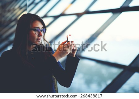 Portrait of attractive young woman taking photo with mobile cell phone sitting near big window of airport hall