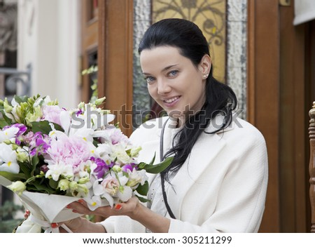 Portrait of attractive young woman with floral bouquet in outdoors flower-shop