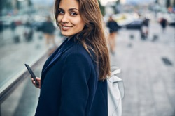Portrait of attractive young woman with mobile in casual clothes smiling while looking into camera