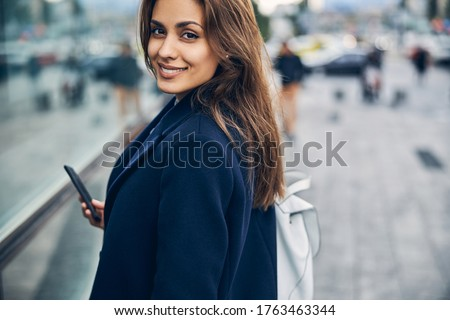 Portrait of attractive young woman with mobile in casual clothes smiling while looking into camera Foto d'archivio ©