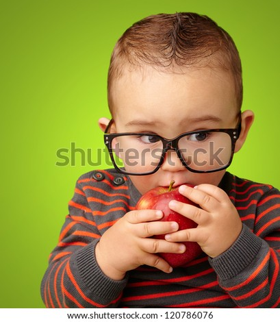 Portrait Of Baby Boy Eating Red Apple against a green background