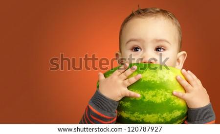 Portrait Of Baby Boy Eating Watermelon against an orange background