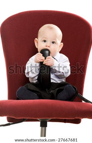Portrait of baby boy sitting on arm-chair with phone receiver in his mouth - stock photo